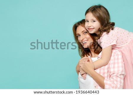Happy woman in pink clothes have fun with cute child baby girl 5-6 years old Mommy little kid daughter stand behind hug isolated on pastel blue azure background studio Mother's Day love family concept