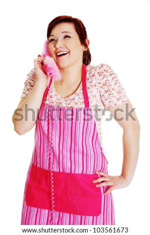 Happy woman in pink kitchen apron talking on the phone. Isolated on white background