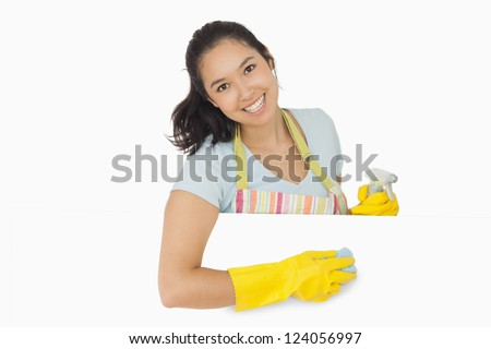 Happy woman in rubber gloves and apron wiping white surface - stock photo