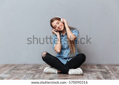 Happy Woman in shirt listening music on the floor with closed eyes. Isolated gray background