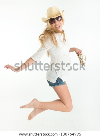 Happy woman in shorts, jumping while holding her shoes