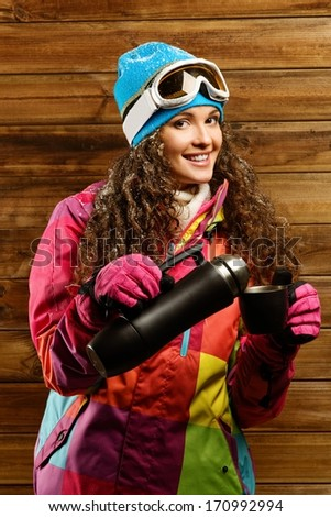 Happy woman in ski wear with thermos against wooden wall