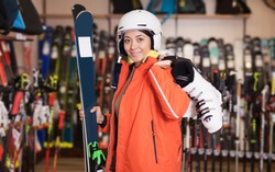 Happy woman in skiing outfit standing with purchased ski equipment in shop