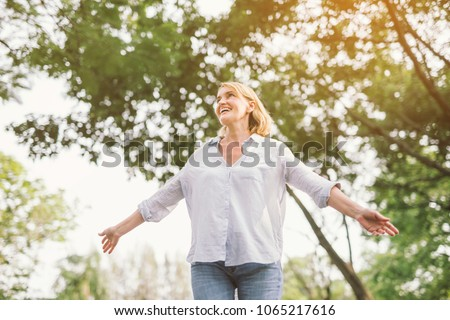 happy woman in spring or summer forest park open arms with happiness, hope and vitality. Caucasian girl relaxing and enjoying life on nature outdoors.