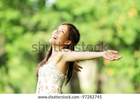 Happy woman in spring / summer smiling carefree and joyful in summer dress in beautiful park. Aspirational freedom concept with beautiful mixed race asian / caucasian girl