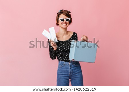 Happy woman in sunglasses holding valise. Studio shot of girl with tickets isolated on pink.