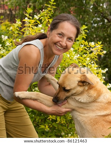 Happy woman in the garden playing with her dog