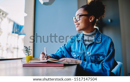 Happy woman in trendy eyewear feeling excited from learning in cafeteria, positive african hipster girl looking away while preparing for college course work sitting with textbooks for education