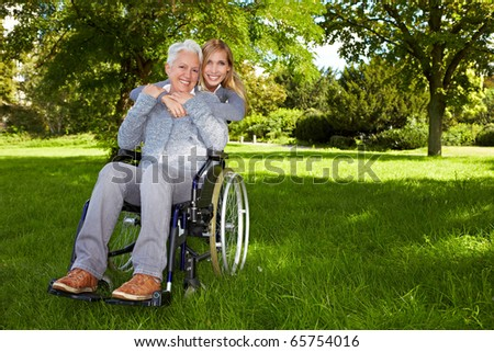 Happy woman in wheelchair with young woman in nature