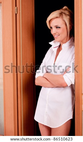 Happy woman in white shirt at the door