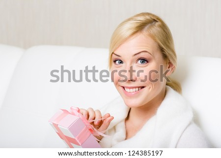 Happy woman in white sweater holds a gift wrapped with pink paper and pink ribbon