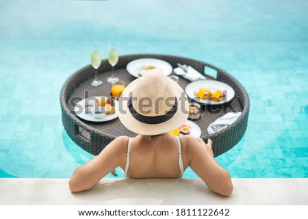 Happy woman in white swimsuit having Floating Breakfast tray in luxury pool hotel, young female with hat enjoy in tropical resort. Relaxing, Exotic summer travel, holiday, vacation and weekend
