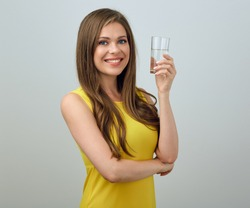 Happy woman in yellow dress holding water glass. isolated female portrait.