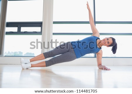 Happy woman in yoga pose in fitness studio
