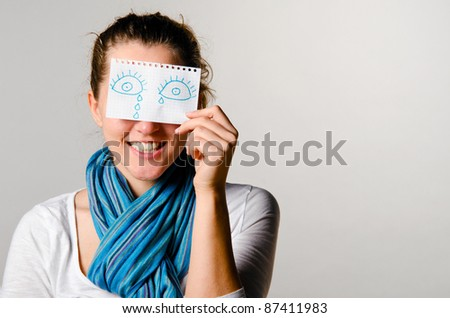 Stock Photo happy woman is holding paper with drawn tears