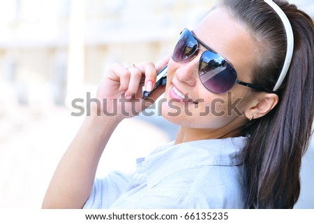 happy woman is looking back and talking phone
