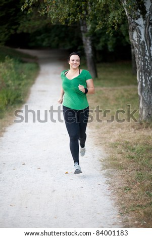 Happy woman jogging in a park/forrest to loose weight