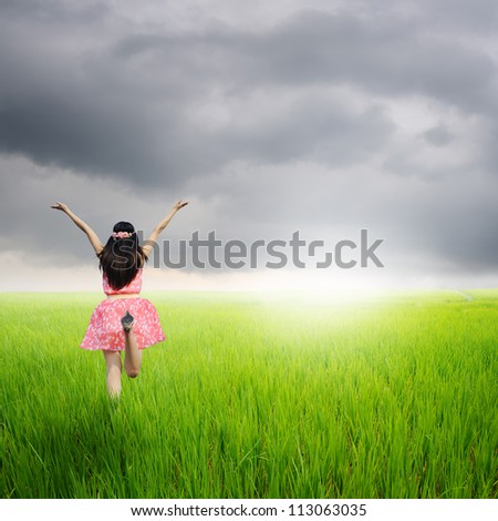 Happy woman jump in green rice fields and rainclouds
