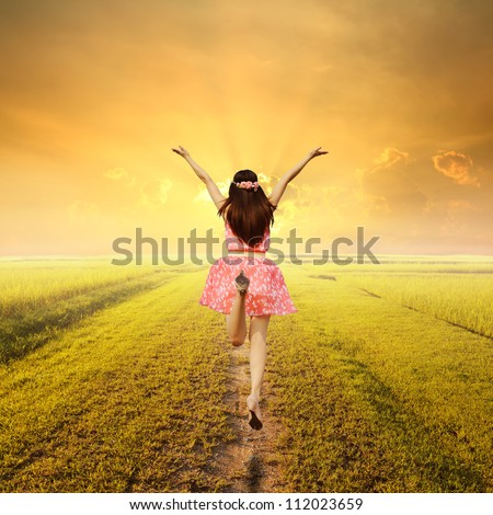 Happy woman jump on way of green grass and sunset