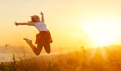 Happy woman   jump,  rejoices, laughs  on sunset in nature