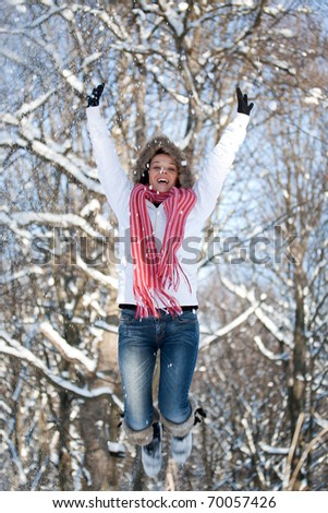 Happy woman jumping and taking pleasure on snowy winter day