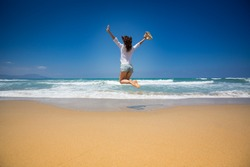 Happy woman jumping at the beach against blue sky and sea background. Summer vacations concept