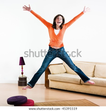 happy woman jumping in a living room