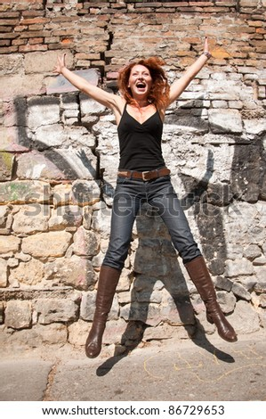 happy woman jumping in front the wall