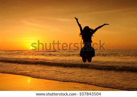 Happy Woman Jumping in Sea Sunset - stock photo