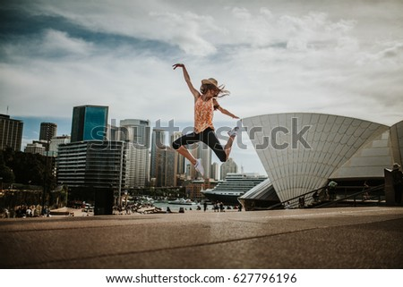 Happy woman jumping in the air in Sydney, with the cityscape in the background. - Shutterstock ID 627796196