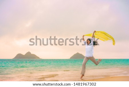 Happy woman jumping of joy and freedom running with yellow scarf in wind on Hawaii beach, Lanikai, Oahu, USA. Summer vacation fun free funny girl.
