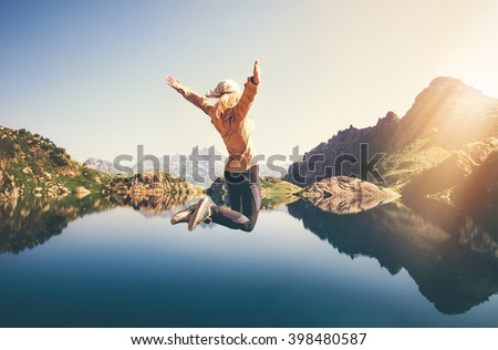 Happy Woman jumping up Flying levitation with lake and mountains on background Lifestyle Travel emotions concept outdoor