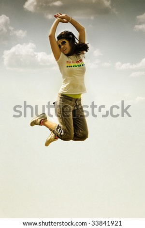 Happy woman jumps against blue sky