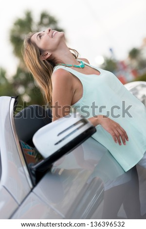 Happy woman leaning on the door of her car