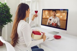 Happy woman looking at man on computer screen and giving toast on romantic virtual date. Couple in love raising glasses and drinking wine together, celebrating Saint Valentine's Day via video call