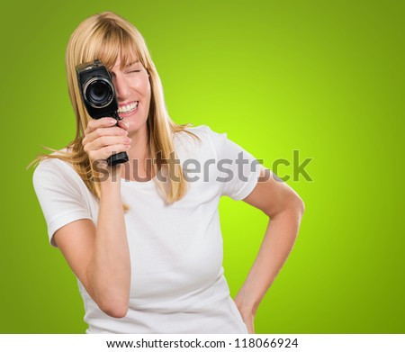 Happy Woman Looking Through Camera against a green background