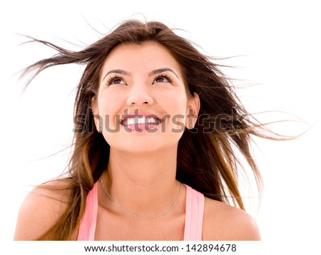 Happy woman looking up in the wind - isolated over white