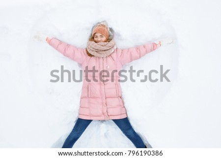 happy woman lying in the snow and moving arms and legs up and down, creating the shape of a snow angel. Smiling woman lying on snow in winter holiday ,for advertising ,background image