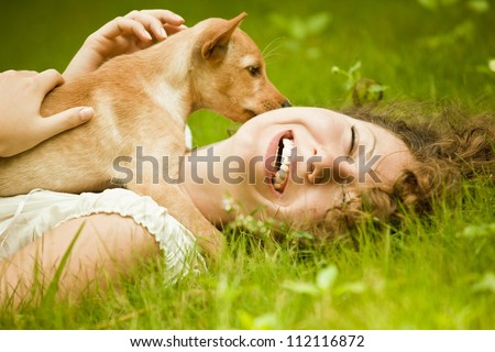 Happy woman lying on the grass with her dog in the park