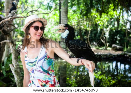 Happy woman make a photo with hornbills on hand in Bird Park on Bali