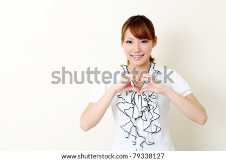 Happy woman make heart shape by her hands