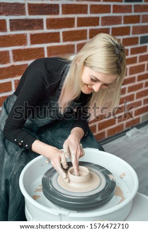 Happy woman making ceramic pottery on wheel. Concept for woman in freelance, business, hobby. Earn extra money, turning hobbies into cash and passion into a job. Female smiling #1576472710