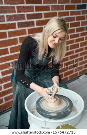 Happy woman making ceramic pottery on wheel. Concept for woman in freelance, business, hobby. Earn extra money, turning hobbies into cash and passion into a job. Beautiful female smiling #1576472713