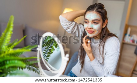 Happy woman making facial massage with organic face scrub and looking at mirror at home. Girl applying scrub cream, peeling and cleaning skin. Skin Care. Attractive girl with moisturizing facial mask