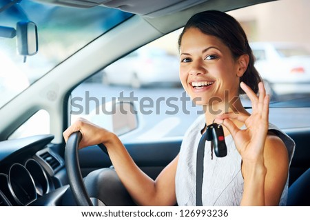 Happy woman new car owner smiling and showing keys in driver seat