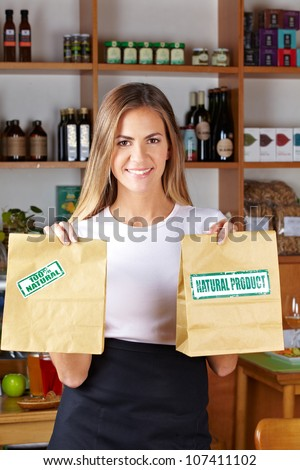Happy woman offering paper bags in a health food store