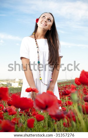 Happy woman on a filed with poppy