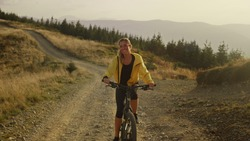 Happy woman on bicycle riding on mountain path. Female bicyclist exercising in mountain landscape. Smiling girl on bike riding on road. Fit athlete enjoying training outdoor