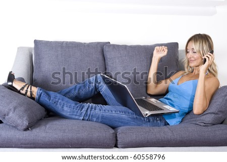 happy woman on her couch with her cellphone and laptop