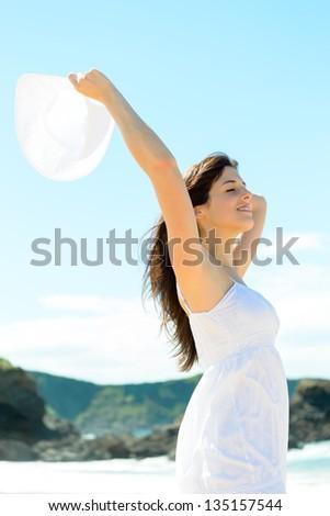 Happy woman on nature beach on summer vacation. Beautiful caucasian girl raising arm and holding white hat. Playa de Verdicio, Asturias, Spain.